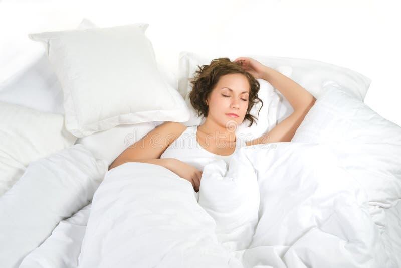 Den unga kvinnan sover på vit linne fotografering för bildbyråer