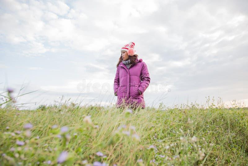 Den unga kvinnan spelade i ett f?lt av blommor i vinterluften arkivbild