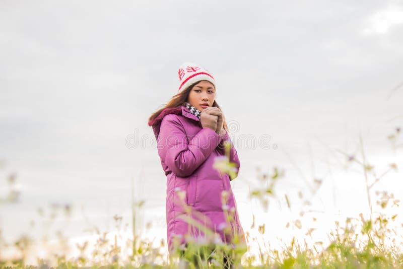 Den unga kvinnan spelade i ett f?lt av blommor i vinterluften royaltyfria foton