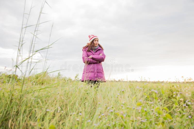 Den unga kvinnan spelade i ett f?lt av blommor i vinterluften arkivbilder