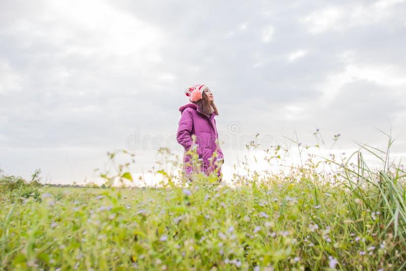 Den unga kvinnan spelade i ett f?lt av blommor i vinterluften fotografering för bildbyråer