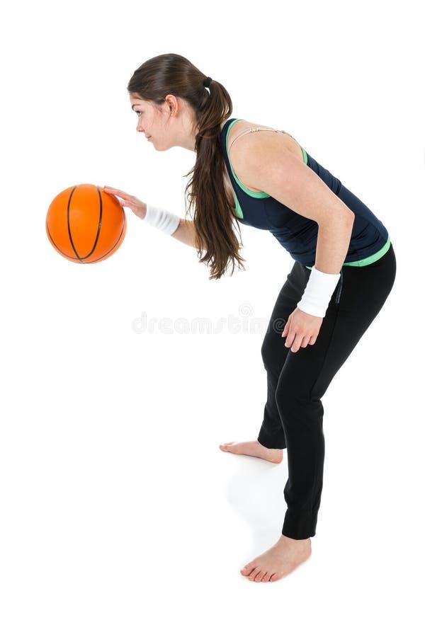 Den unga kvinnan spelar basket som isoleras över vit arkivbild
