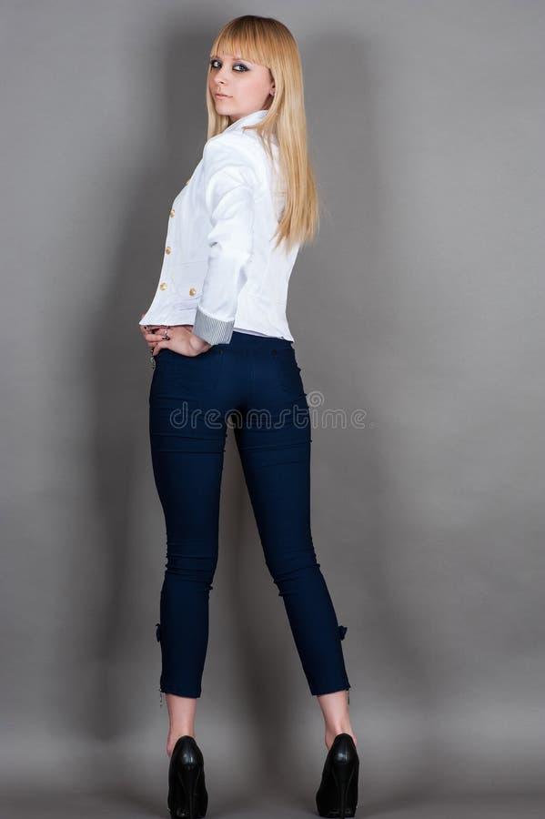 den unga kvinnan står halv vänd för full längd royaltyfri foto