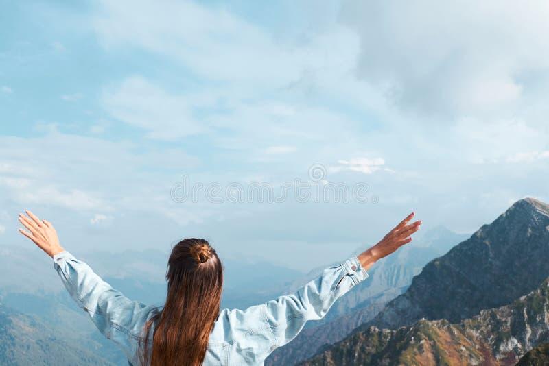 Den unga kvinnan står i berget med utsträckta armar Frihets- och lyckabegrepp med kopieringsutrymme arkivbilder