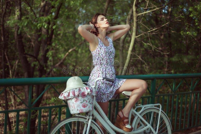 Den unga kvinnan står med en cykel på bron arkivbild