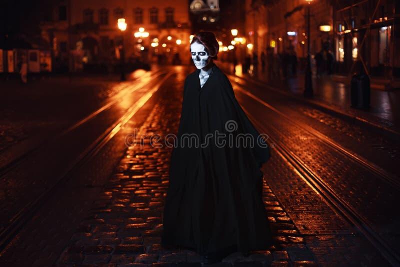 Den unga kvinnan står på gatan i svart dräkt med allhelgonaaftonmakeup Fulbody stående arkivfoto