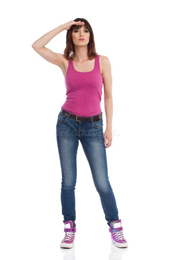 Den unga kvinnan står, rymmer handen på pannan och ser bort royaltyfri foto