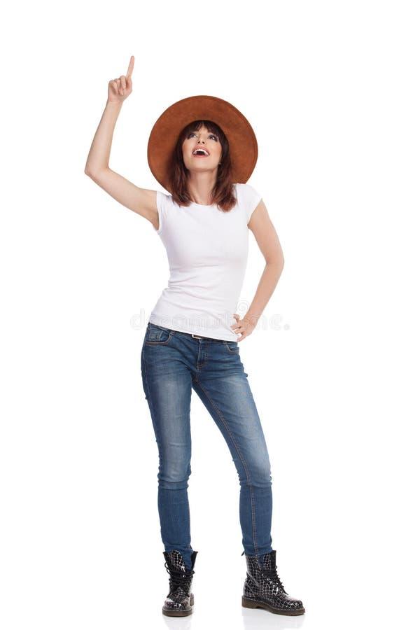 Den unga kvinnan står, ser bort och pekar upp fotografering för bildbyråer