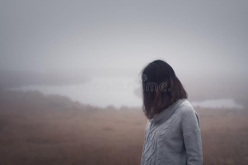 Den unga kvinnan står vid vattnet i dimman på en dimmig dag royaltyfri bild