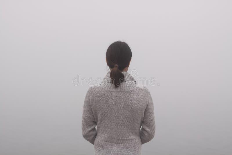 Den unga kvinnan står vid vattnet på en dimmig dag arkivbild