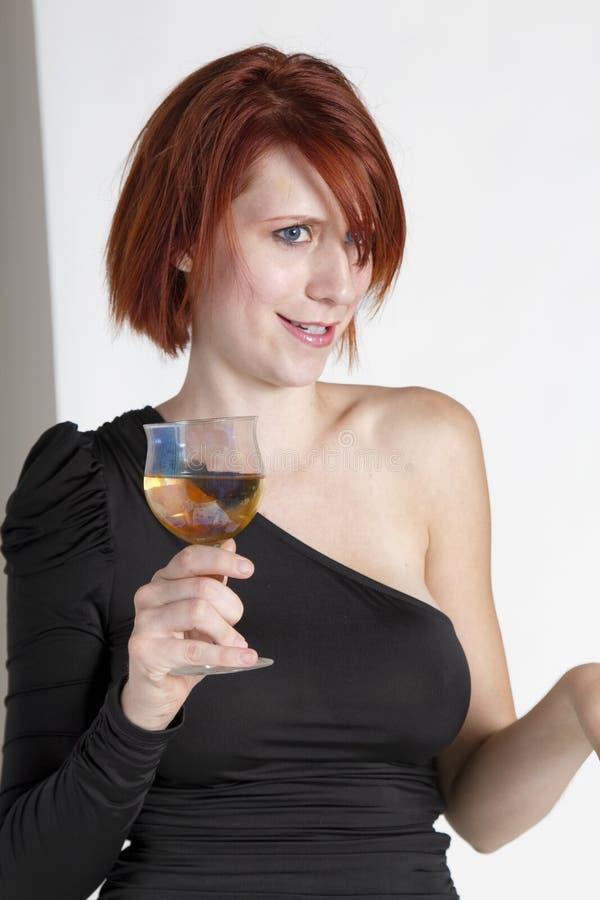 Den unga kvinnan stirrar innehavet hennes exponeringsglas av vin royaltyfria bilder