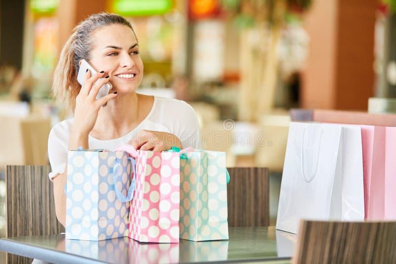 Den unga kvinnan talar p? mobiltelefonen royaltyfria bilder