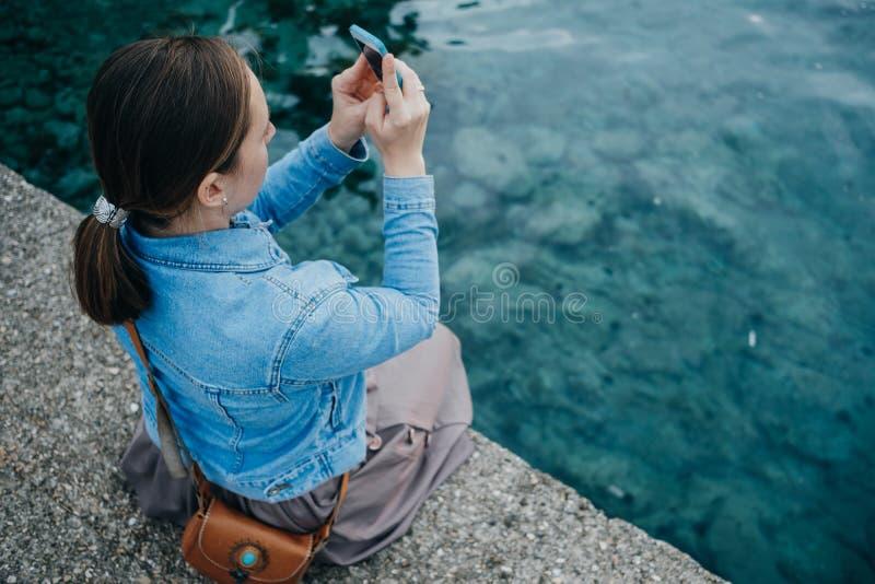 Den unga kvinnan tar bilder av solnedgången på telefonen vid royaltyfri foto
