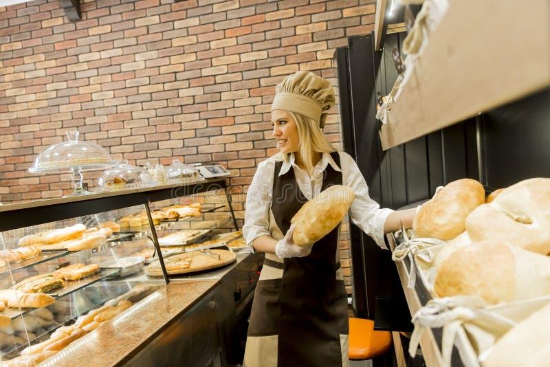 Den unga kvinnan tar nytt bröd från hyllorna i en bagare shoppar royaltyfri bild