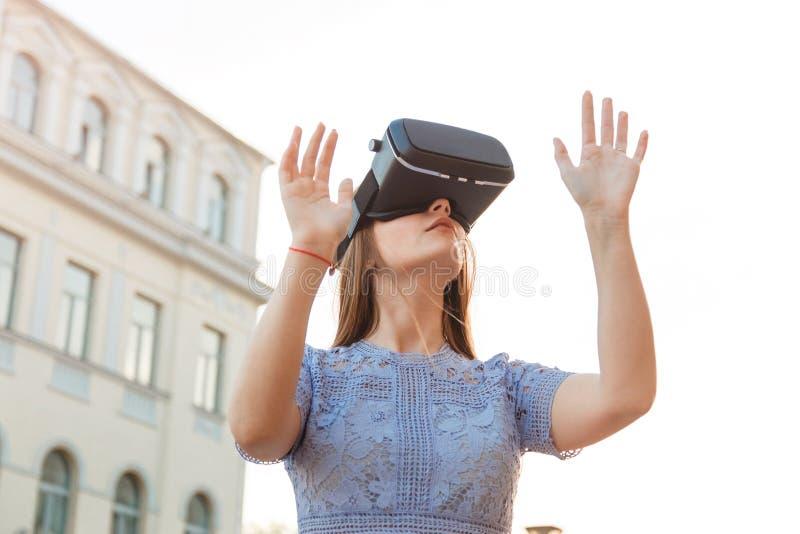 Den unga kvinnan tycker om med den utomhus- VR-apparaten royaltyfri fotografi