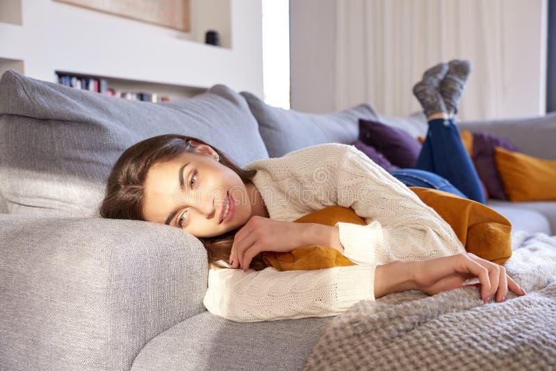 Den unga kvinnan tycker om morgonsolsken, medan koppla av på soffan hemma royaltyfri bild