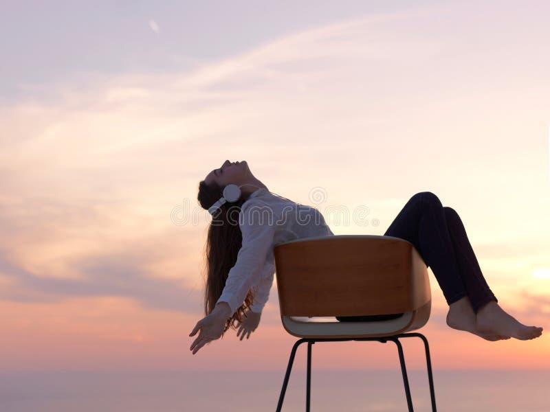 Den unga kvinnan tycker om solnedgång arkivbild