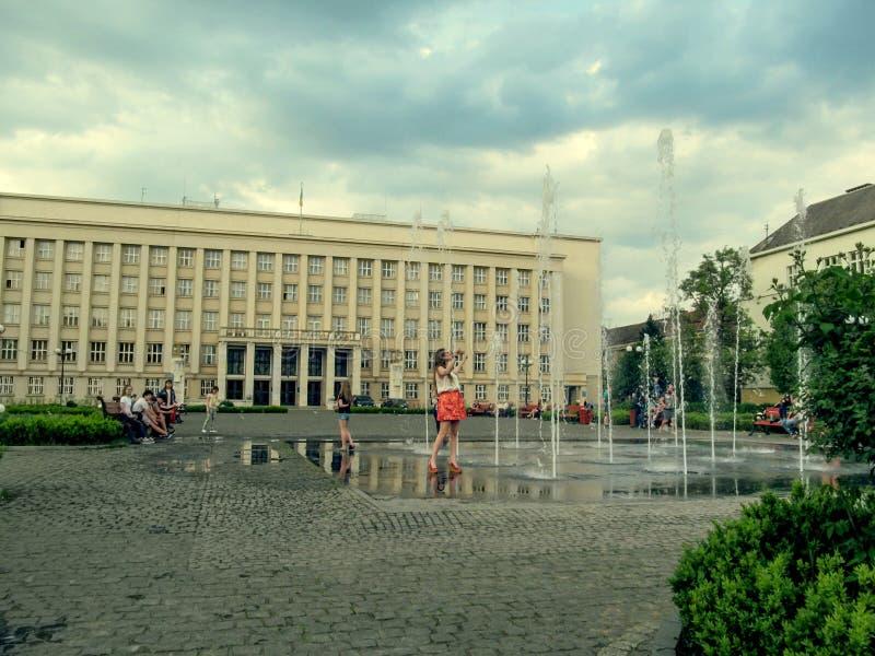 Den unga kvinnan tycker om springbrunnen på den Narodna fyrkanten i Uzhgorod arkivfoton