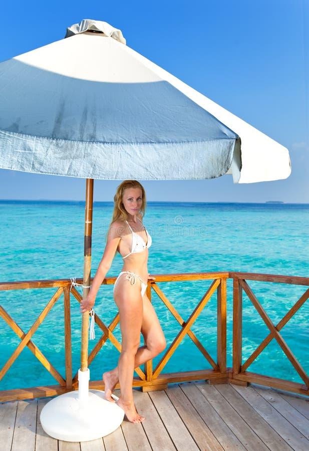 Den unga kvinnan under ett paraply royaltyfria bilder