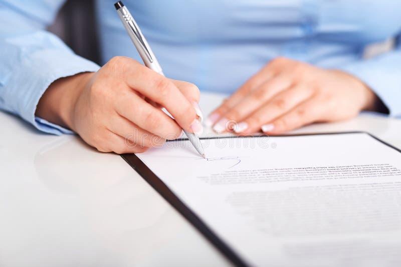 Den unga kvinnan undertecknar ett avtal arkivfoto