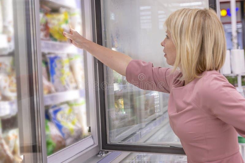 Den unga kvinnan väljer djupfryst mat i kylen av en supermarket N?rbild royaltyfria bilder