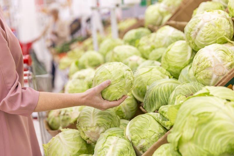 Den unga kvinnan väljer ett kålhuvud i supermarket N?rbild arkivbilder