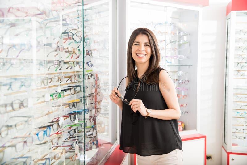 Den unga kvinnan väljer exponeringsglas i optikerlager arkivbilder