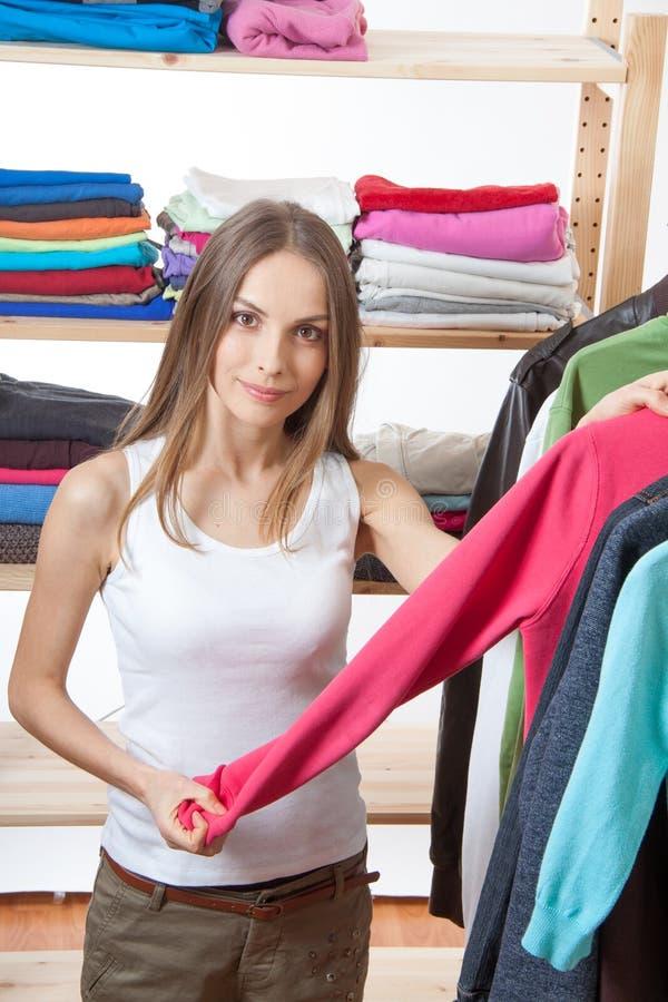 Den unga kvinnan väljer kläder arkivfoton
