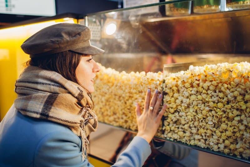 Den unga kvinnan väljer popcorn på bion Mat och mellanm?l arkivfoton