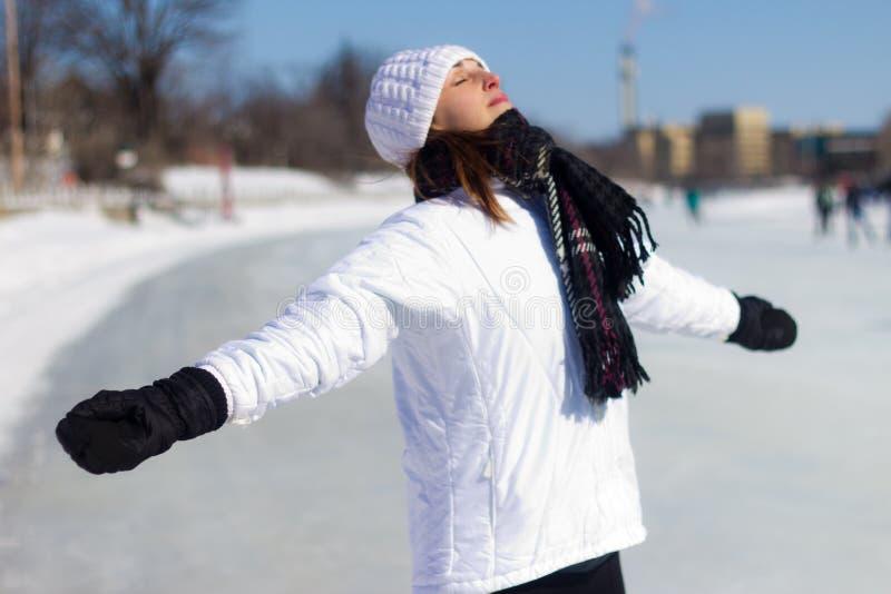 Den unga kvinnan välkomnar solen på en kall vinterdag royaltyfri foto