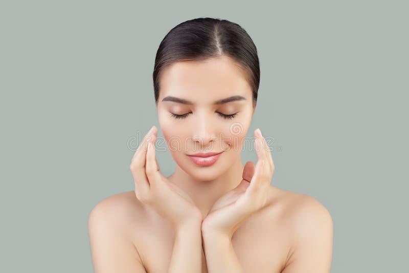 Den unga kvinnan vänder mot Le modellen med sund hud på grå bakgrund royaltyfria foton