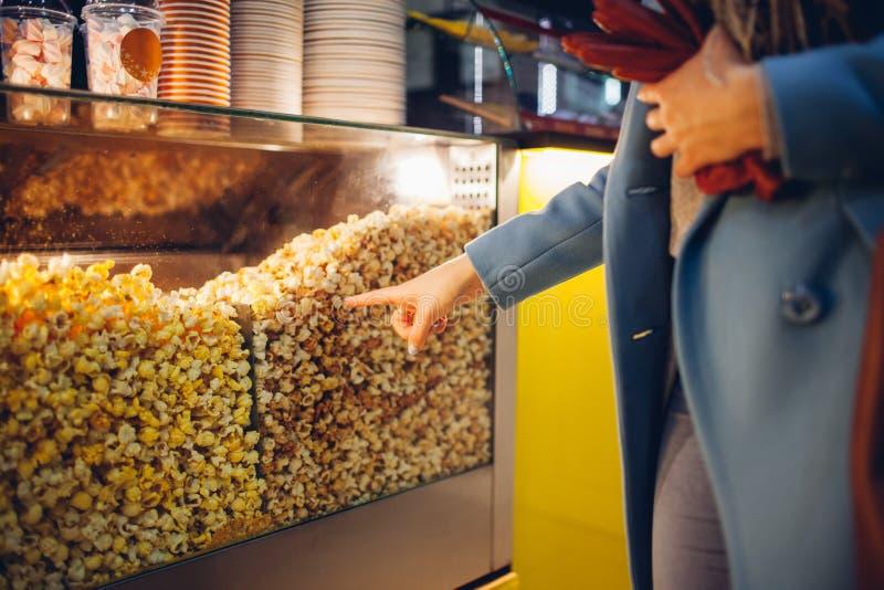 Den unga kvinnan v?ljer popcorn p? bion Mat och mellanm?l royaltyfria bilder