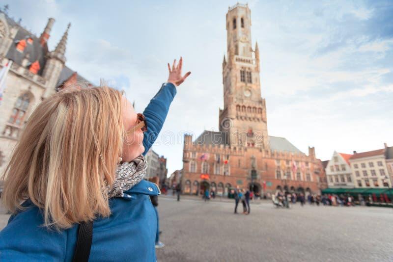 Den unga kvinnan visar handen på det Belfort tornet i Bruges, Belgien arkivfoton