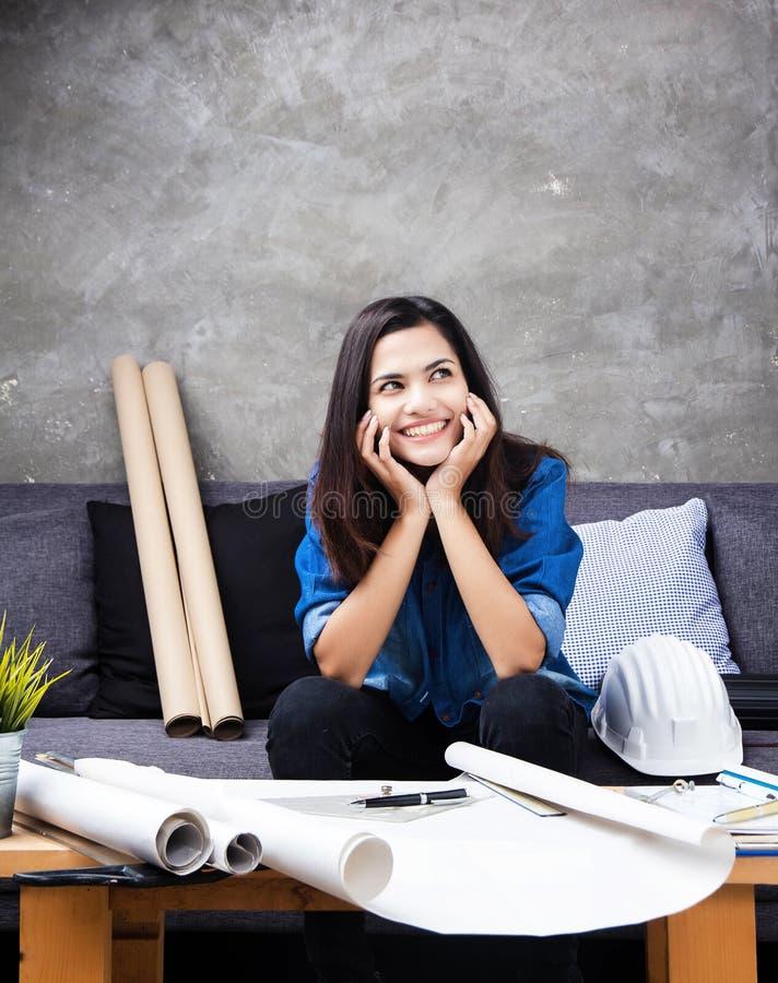 Den unga kvinnliga arkitekten som arbetar på projekt, med leende och den lyckliga framsidan, vilar hakan på händer, överflöd av n arkivfoton