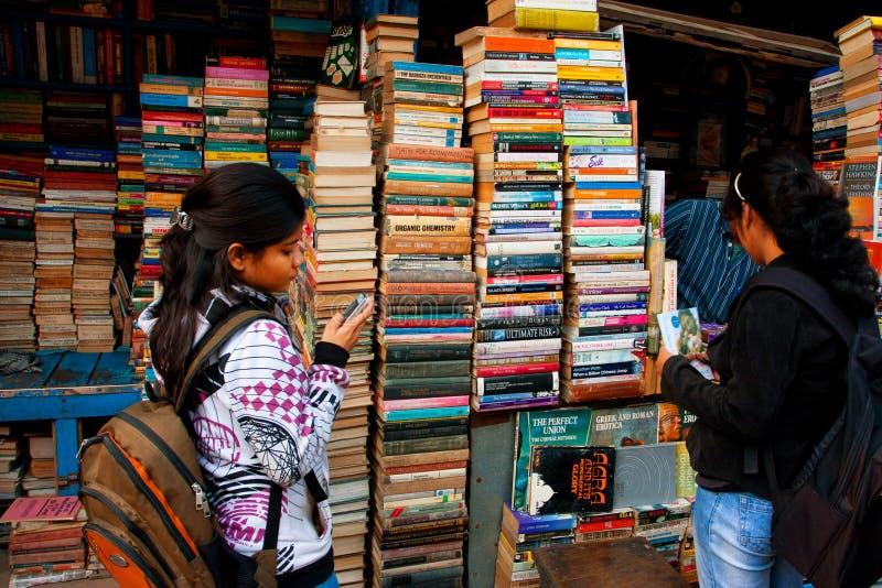 Den unga kvinnliga deltagaren väljer boka på gatan marknadsför arkivfoto