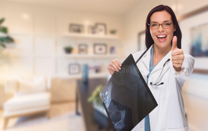 Den unga kvinnliga doktorn eller sjuksköterskan med tummar Up H för anseendet i regeringsställning arkivfoto