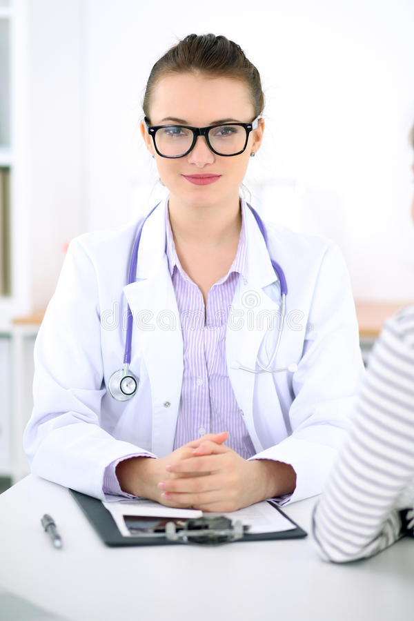 Den unga kvinnliga doktorn lyssnar till den tålmodiga berättelsen försiktigt Läkarundersökning- och sjukvårdbegrepp royaltyfri fotografi