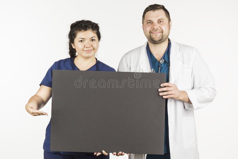 Den unga kvinnliga doktorn och mandoktorn visar upp på en tom billboa royaltyfria bilder