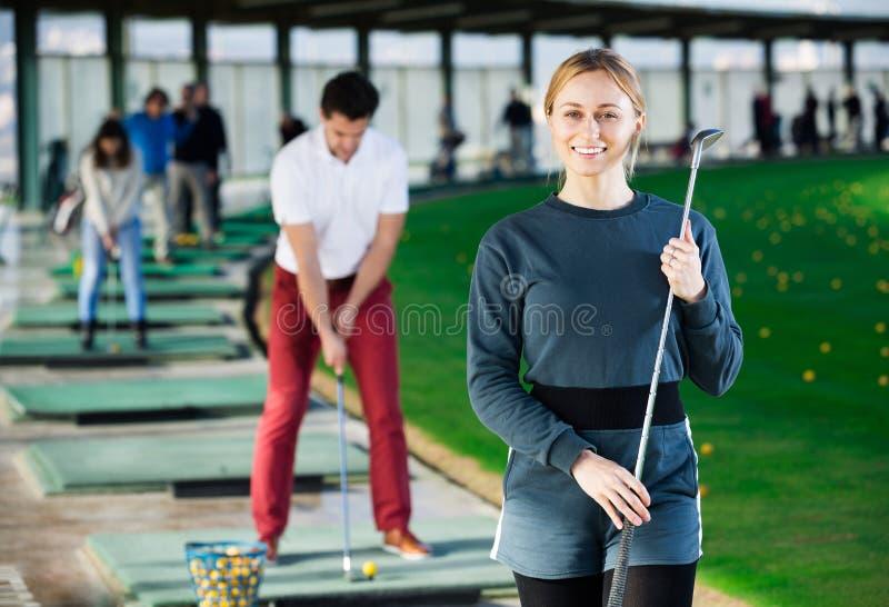 Den unga kvinnliga golfaren är klar för lek arkivfoto