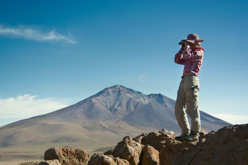 Den unga kvinnliga handelsresanden använder kikare i bergen royaltyfria foton