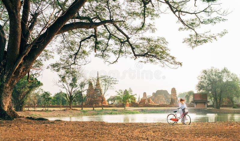 Den unga kvinnliga handelsresanden weared ljus sommarkläder, och hatten har otta att gå med cykeln nära historiska Ayutthaya park arkivbilder