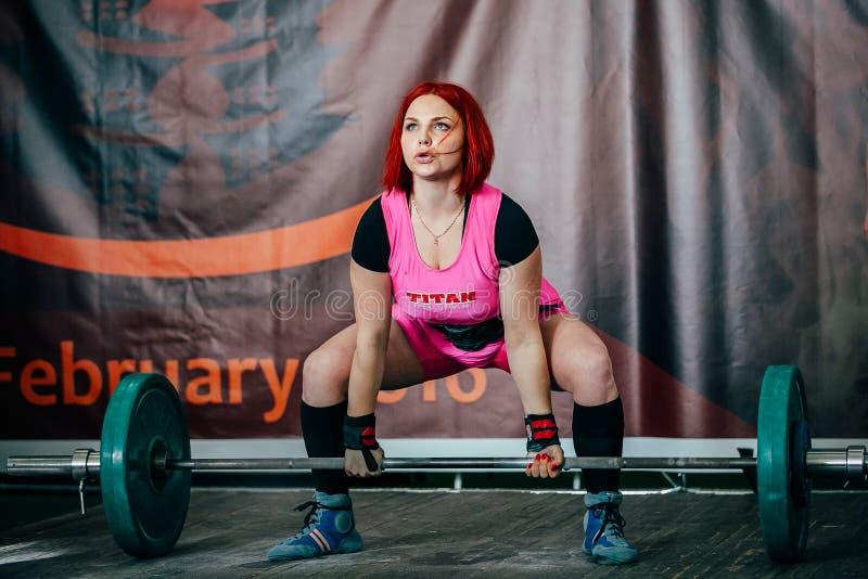 Den unga kvinnliga idrottsman nen utför deadliftskivstången arkivbild
