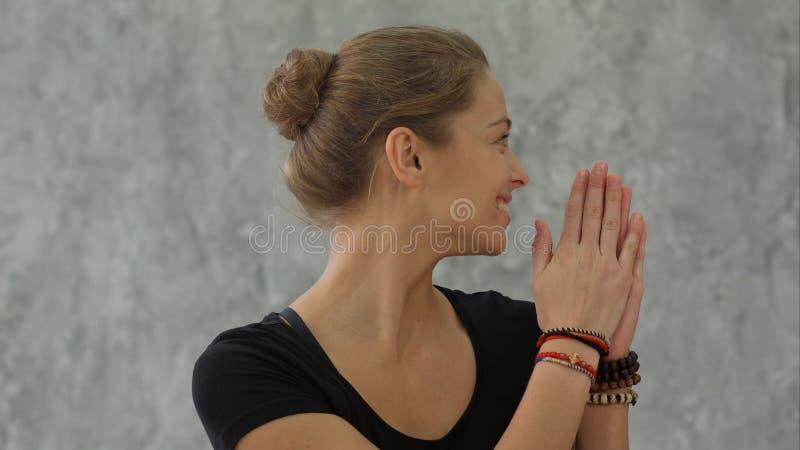 Den unga kvinnliga instruktören som gör namaste, poserar och ler, den välkomna gruppen för yogagrupp fotografering för bildbyråer