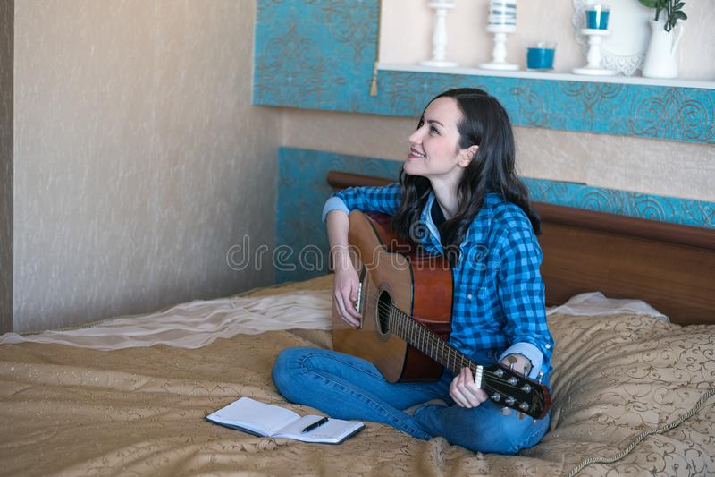 Den unga kvinnliga kompositören komponerar en sång på den akustiska gitarren på säng i sovrum arkivbild