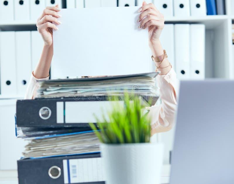 Den unga kvinnliga kontorsarbetaren döljer bak mappen som rymmer det rena vita arket av papper Begrepp av låg lön, länge arkivfoto