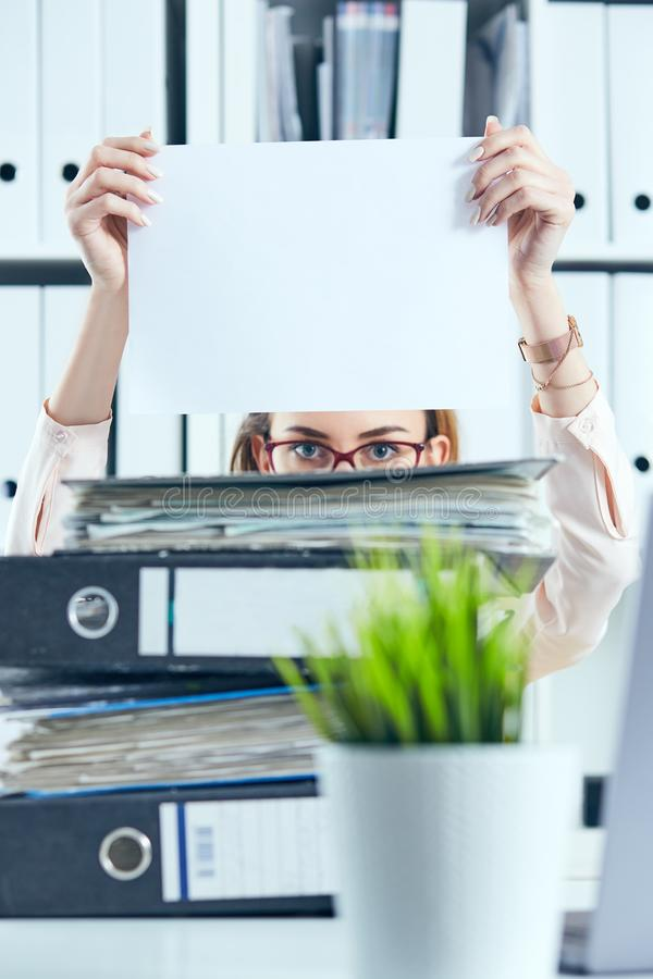 Den unga kvinnliga kontorsarbetaren döljer bak mappen som rymmer det rena vita arket av papper Begrepp av låg lön, länge royaltyfria foton
