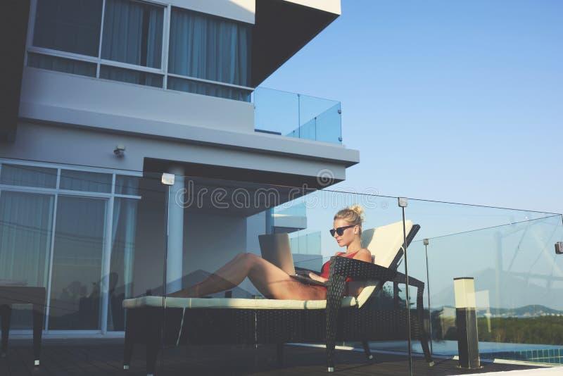 Den unga kvinnliga lyckade freelanceren i solglasögon använder bärbar datordatoren för avlägset arbete royaltyfri bild