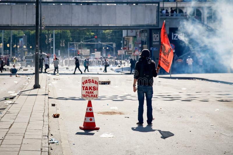 Den unga kvinnliga personen som protesterar som rymmer en flagga som kämpar mot tårgasen som avfyras av polisen under Gezi, parke royaltyfria bilder