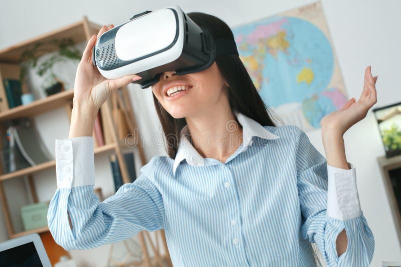 Den unga kvinnliga resebyråmankonsulenten turnerar in byrån som spelar virtuell verklighethörlurar med mikrofon royaltyfria bilder