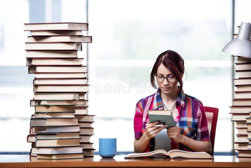 Den unga kvinnliga studenten som förbereder sig för examina arkivbilder